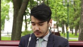 Hombre de negocios asiático del hombre que se sienta en parque y que come las patatas fritas almacen de video