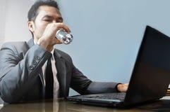 Hombre de negocios asiático en agua potable del traje gris El usar y retrete del hombre foto de archivo libre de regalías