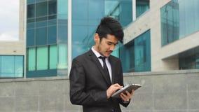 Hombre de negocios asiático feliz que usa la tableta para el trabajo almacen de video