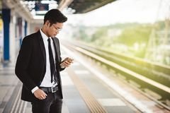 Hombre de negocios asiático joven del inconformista con el smartphone que espera en la plataforma del tren fotografía de archivo