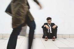 Hombre de negocios asiático joven desaliñado que se sienta en la calzada que piensa en su problema foto de archivo