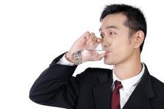 Hombre de negocios asiático joven que bebe un vidrio de agua, aislado en blanco Imágenes de archivo libres de regalías