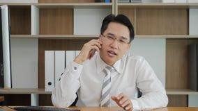 Hombre de negocios asiático joven que habla en el teléfono celular en la oficina almacen de video