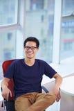 Hombre de negocios asiático joven que mira sonrisa de la cámara en oficina Imagen de archivo libre de regalías