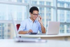 Hombre de negocios asiático joven que trabaja en la oficina Imagenes de archivo