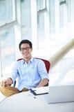 Hombre de negocios asiático joven que trabaja en la oficina Fotos de archivo libres de regalías