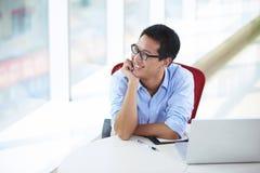 Hombre de negocios asiático joven que trabaja en la oficina Imágenes de archivo libres de regalías