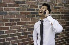 Hombre de negocios asiático Laughing y el hablar en el teléfono móvil Foto de archivo libre de regalías