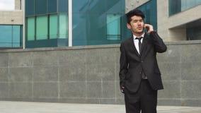 Hombre de negocios asiático que camina y que hace llamadas de teléfono metrajes