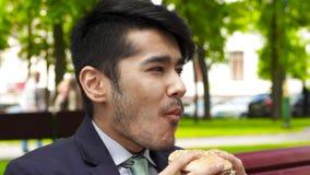 Hombre de negocios asiático que come la hamburguesa sabrosa metrajes