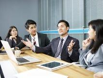 Hombre de negocios asiático que habla en la tabla de la negociación imagen de archivo