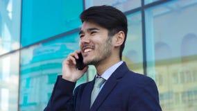 Hombre de negocios asiático que habla por el teléfono metrajes