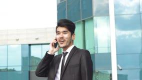 Hombre de negocios asiático que hace llamadas de teléfono metrajes