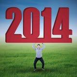 Hombre de negocios asiático que levanta el Año Nuevo 2014 Imagen de archivo libre de regalías