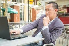 Hombre de negocios asiático que mecanografía en el cuaderno o el ordenador portátil Foto de archivo libre de regalías