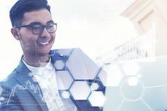 Hombre de negocios asiático que mira el doble del ordenador portátil foto de archivo libre de regalías