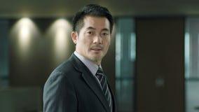 Hombre de negocios asiático que mira la sonrisa de la cámara almacen de metraje de vídeo