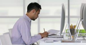 Hombre de negocios asiático que mira para representar gráficamente almacen de video