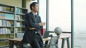 Hombre de negocios asiático que piensa en oficina metrajes