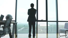 Hombre de negocios asiático que se coloca delante de ventanas en oficina almacen de video