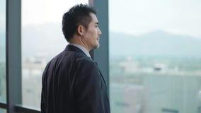 Hombre de negocios asiático que se coloca delante de ventanas en oficina metrajes
