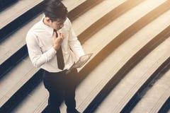 Hombre de negocios asiático que se coloca en la escalera al aire libre y que usa la tableta con la mirada de tecnología financier fotos de archivo libres de regalías