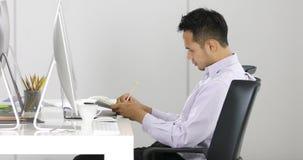 Hombre de negocios asiático que se sienta delante de los ordenadores almacen de metraje de vídeo