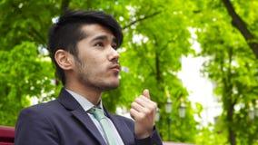 Hombre de negocios asiático que se sienta en parque y que come las patatas fritas almacen de video