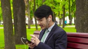 Hombre de negocios asiático que se sienta en parque y que come las patatas fritas en auriculares almacen de video