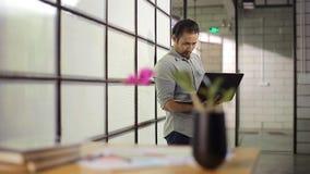 Hombre de negocios asiático que sostiene el ordenador portátil que piensa en oficina almacen de metraje de vídeo