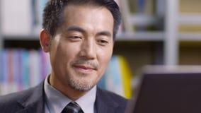 Hombre de negocios asiático que trabaja en oficina almacen de metraje de vídeo