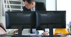 Hombre de negocios asiático que usa el cuaderno en oficina almacen de video