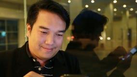 Hombre de negocios asiático que usa en el teléfono móvil y con el teléfono elegante en la noche en café Hombre hermoso que espera metrajes