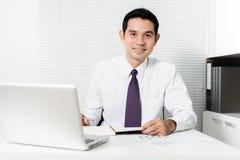 Hombre de negocios asiático sonriente que trabaja en la oficina Imagen de archivo