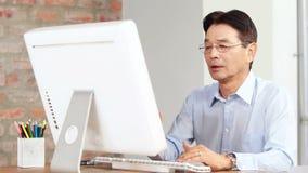 Hombre de negocios asiático usando el ordenador en el escritorio metrajes