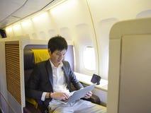 Hombre de negocios asiático usando el ordenador portátil en el aeroplano de la primera clase fotografía de archivo libre de regalías