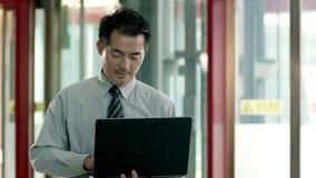 Hombre de negocios asiático usando el ordenador portátil en vestíbulo almacen de metraje de vídeo