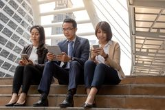 Hombre de negocios asiático y empresarias que discuten ideas con el teléfono móvil digital mientras que se sienta en las escalera imágenes de archivo libres de regalías