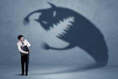 Hombre de negocios asustado de su propio concepto del monstruo de la sombra imágenes de archivo libres de regalías