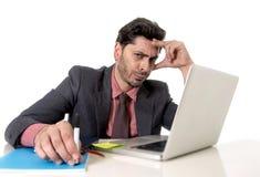 Hombre de negocios atractivo en el escritorio de oficina que trabaja en el ordenador portátil del ordenador que parece cansado y  Foto de archivo