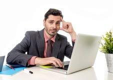 Hombre de negocios atractivo en traje y lazo que trabaja en la tensión en el offi Foto de archivo libre de regalías
