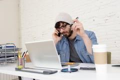 Hombre de negocios atractivo hispánico del inconformista que trabaja en casa la oficina que habla en el teléfono móvil Imagen de archivo libre de regalías