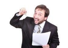 Hombre de negocios atractivo joven con los claves y el papel o imagen de archivo libre de regalías