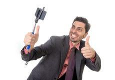 Hombre de negocios atractivo joven en traje y lazo que toma la foto del selfie con la presentación de la cámara y del palillo del Fotos de archivo libres de regalías