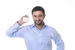 Hombre de negocios atractivo joven feliz que sostiene la tarjeta de visita en blanco con el espacio de la copia Imagen de archivo libre de regalías