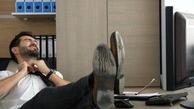 Hombre de negocios atractivo joven que se relaja en su escritorio en la oficina metrajes