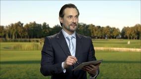 Hombre de negocios atractivo que usa la tableta digital al aire libre
