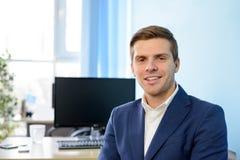 Hombre de negocios atractivo sonriente de los jóvenes en traje azul en la oficina moderna Concepto del asunto fotos de archivo libres de regalías
