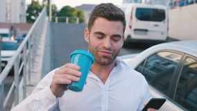 Hombre de negocios atractivo Standing en el aparcamiento cerca del edificio de oficinas Mecanografiar un mensaje en su Smartphone almacen de video