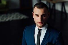 Hombre de negocios atractivo y confiado joven en traje azul y lazo negro Imagenes de archivo